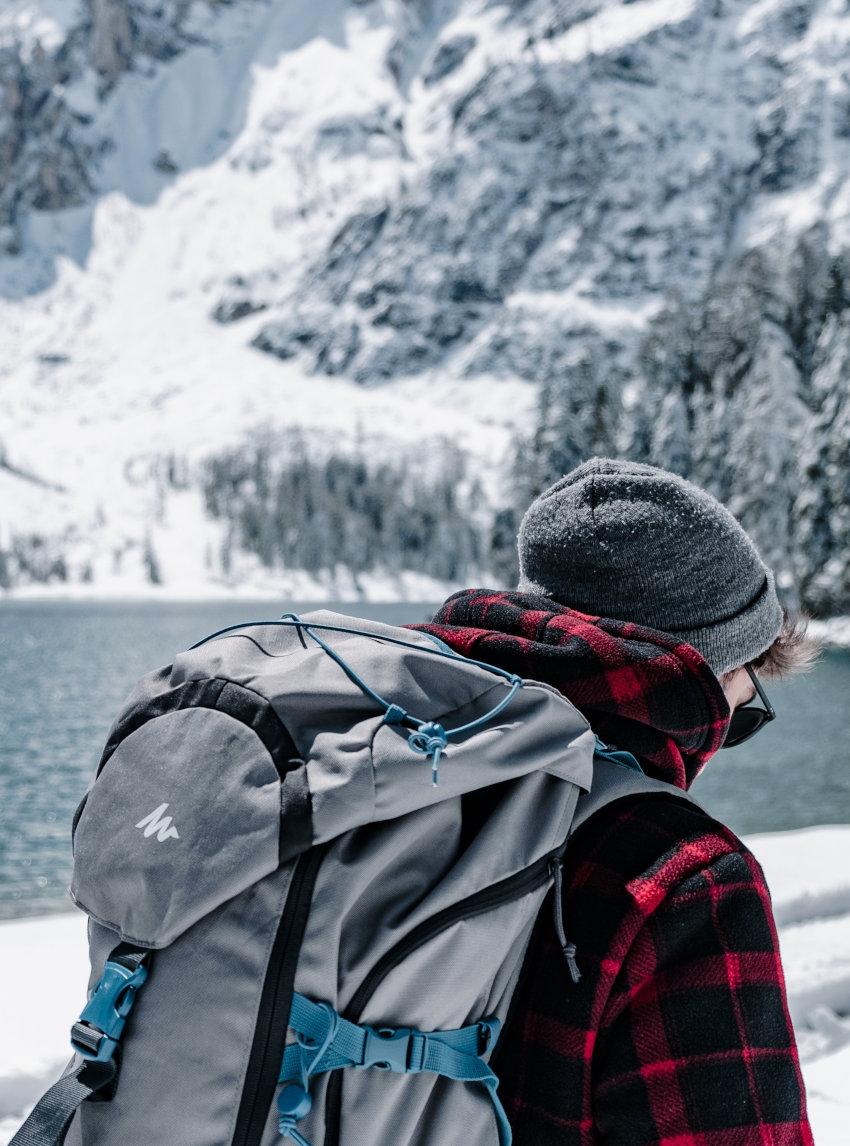 Winterlandschaft mit jungem Mann in Karohemd und einem grauen Backpacker-Rucksack auf dem Rücken