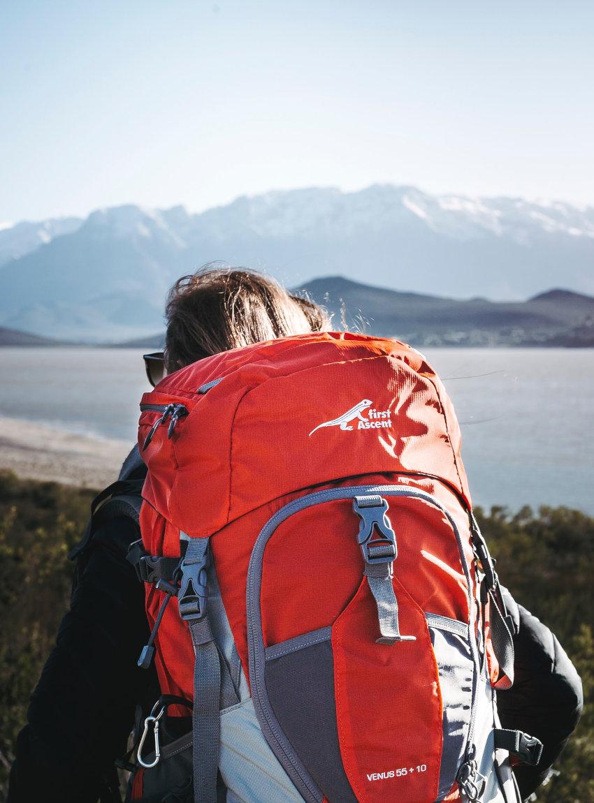 Eine junge Backpackerin samt Trekkingrucksack steht vor eine Kulisse aus See mit Bergen
