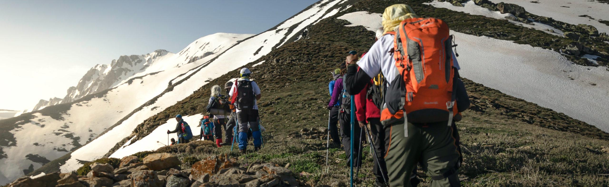 Eine Wandergruppe mit großen Backpacker-Rucksäcken marschiert durch eine Berglandschaft