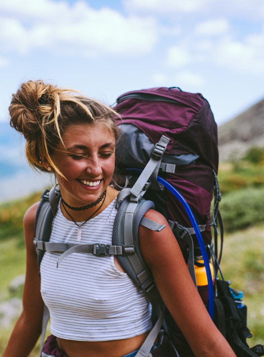 Ein junges Mädchen wandert glücklich mit ihrem Trekkingrucksack durch eine grüne Berglandschaft