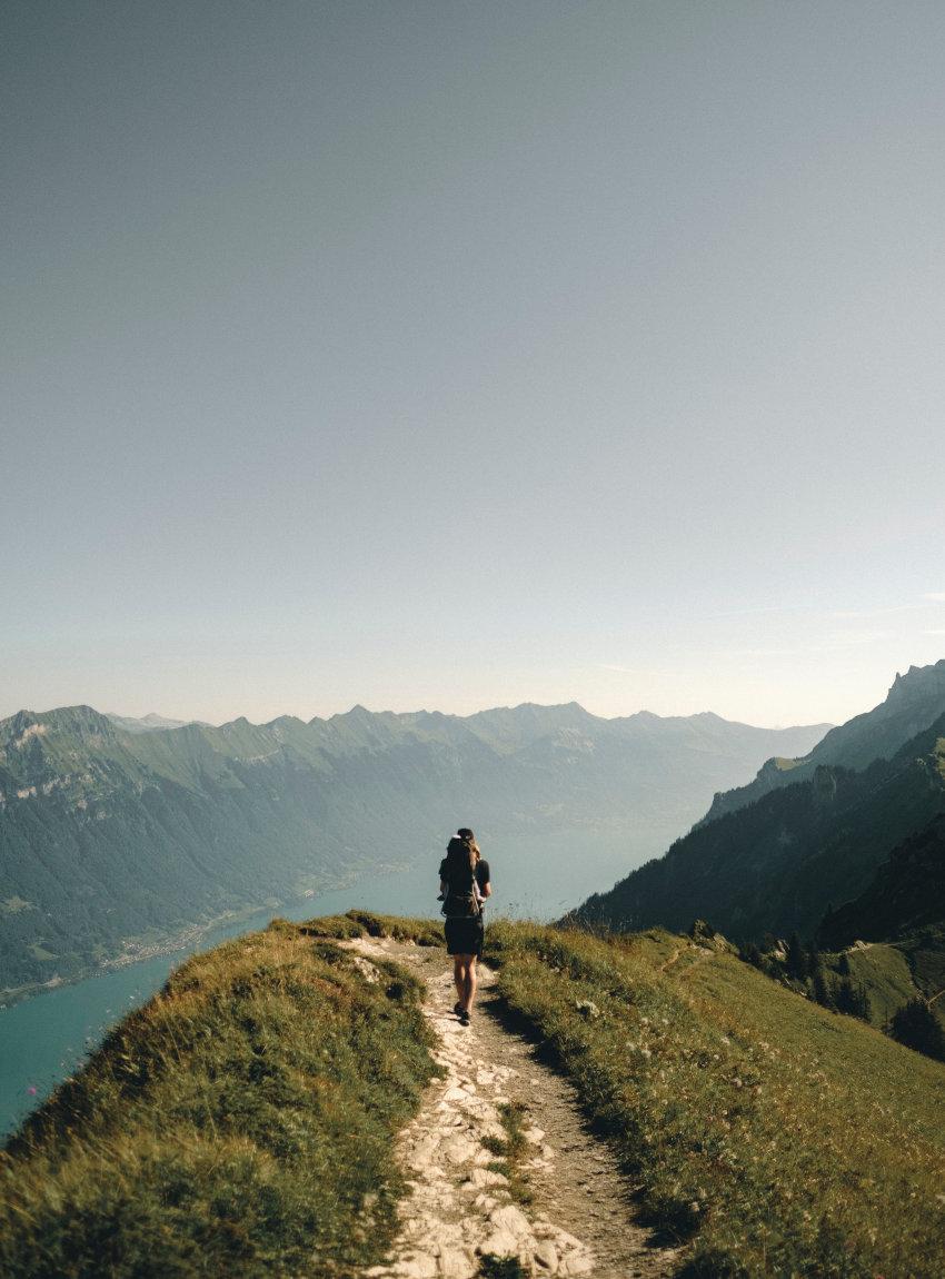 Ein junger Mann wandert mit einem grünen Daypack auf einem Berg mit Blick auf einen See