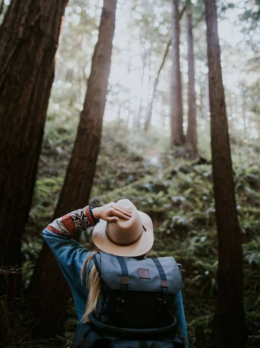 Ein Mädchen steht mit einem dunkelgrauen Daypack im Wald und trägt einen Hut